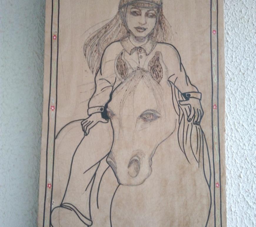 Quadro de madeira desenhado um cavalo com uma amazona com a técnica do pirógrafo nos contornos do desenho.
